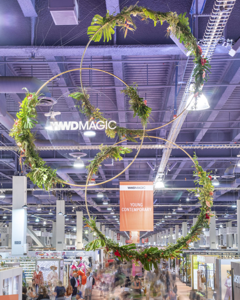 Plant rental display on circular structures hanging from the ceiling above a trade show floor.